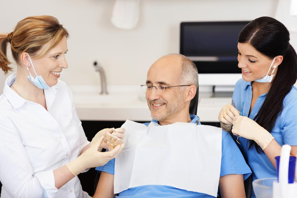 Dentist explaining teeth model to male patient at clinic